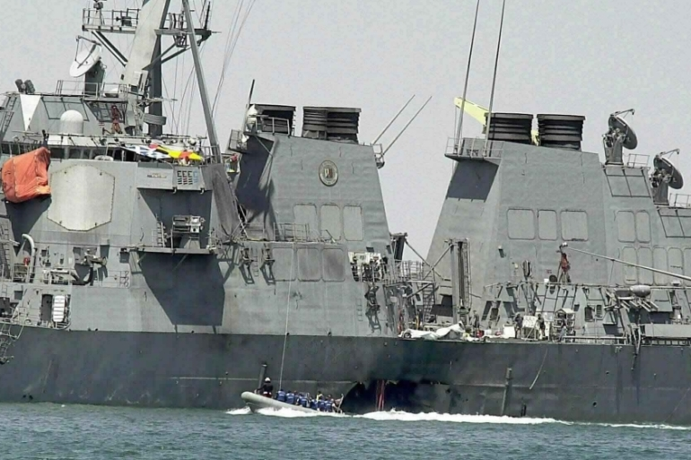In this October 15, 2000 photo, experts in a speedboat examine the damaged hull of the USS Cole at the Yemeni port of Aden [File: Dimitri Messinis/AP Photo]