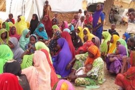 Women and children gather at the Madinatu IDP camp to listen to members of the Borno Community Coalition speak about the dangers of human trafficking [Philip Obaji Jr/Al Jazeera]