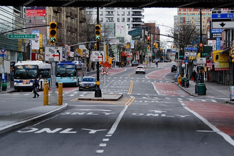 A pedestrian crosses the street in the Queens borough of New York [Frank Franklin II/AP Photo]