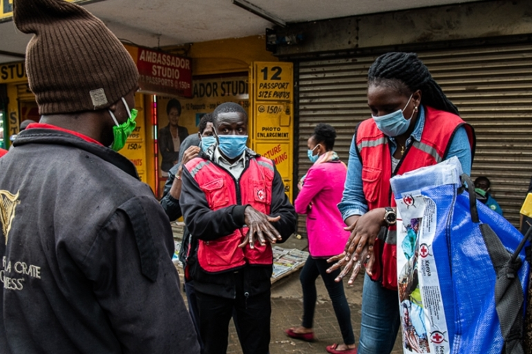 A member of Kenya Red Cross demonstrates hand-washing to members of the deaf community in Nairobi amid the COVID-19 pandemic [Georgina Smith/Al Jazeera]