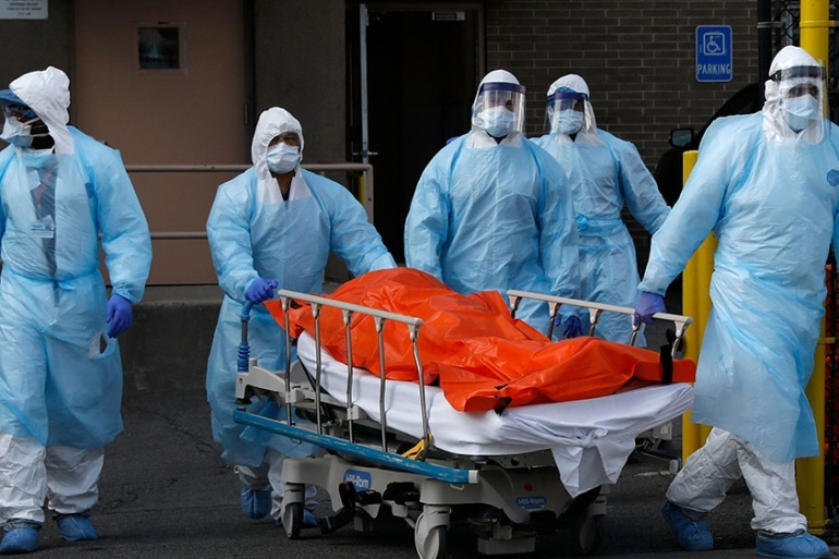 Healthcare workers wheel the body of deceased person from the Wyckoff Heights Medical Center during the outbreak of the coronavirus disease (COVID-19) in the Brooklyn borough of New York City [Brendan Mcdermi/Reuters]