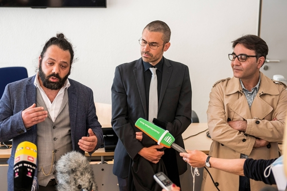 Lawyer Patrick Kroker, centre, and co-plaintiffs Wassim Mukdad, left, and Hussein Ghrer, right, answer questions outside the German courtroom during a break in the trial against two Syrian defendants accused of state-sponsored torture [File: Thomas Lohnes/AFP]