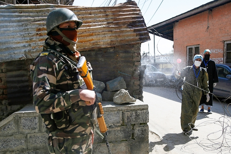 An Indian paramilitary soldier stands guard as a Kashmiri volunteer sprays disinfectant as a precautionary measure against the new coronavirus in Srinagar [File: Mukhtar Khan/AP Photo]
