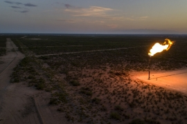 A gas flare burns at dusk in the Permian Basin in Texas, US, where storage facilities are filling as the coronavirus continues to seep global oil demand and state regulators weigh ways to help the shale industry manage an historic crash in prices [File: Bronte Wittpenn/Bloomberg]