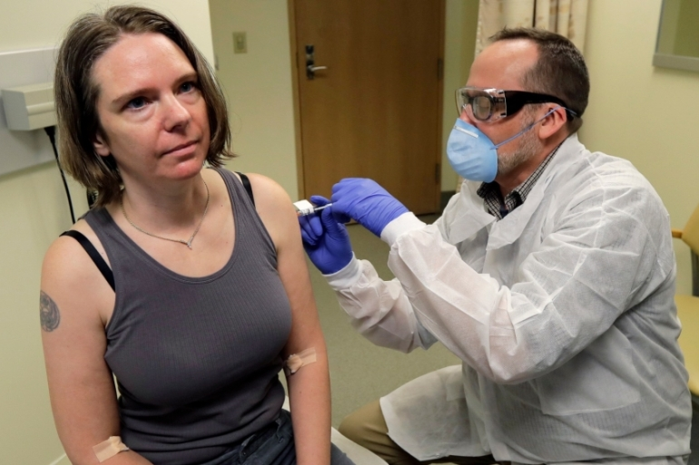 A pharmacist gives Jennifer Haller, left, the first shot in the first-stage safety study clinical trial of a potential vaccine for COVID-19, the disease caused by the new coronavirus, on March 16, 2020, at the Kaiser Permanente Washington Health Research Institute in Seattle [Ted S Warren/AP]
