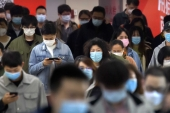 Commuters wear face masks to protect against the spread of new coronavirus as they walk through a subway station in Beijing, on April 9, 2020 [AP/Mark Schiefelbein]