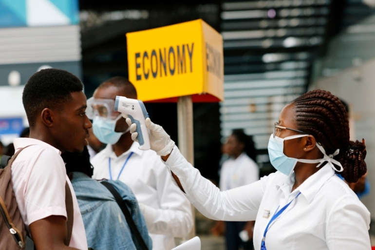 A health worker checks the temperature of a traveller as part of the coronavirus screening procedure at the Kotoka Airport in Accra, Ghana on January 30, 2020 [File: Reuters/Francis Kokoroko]