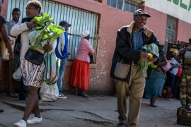 People leave a vegetable wholesaler after buying their fresh produce under the watch of a joint military and police patrol in Bulawayo, Zimbabwe [Tendai Marima/Al Jazeera]