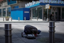 A Muslim woman kneels for midday prayers in a nearly empty Times Square in Manhattan during the outbreak of the coronavirus disease (COVID-19) in New York City, New York [Mike Segar/Reuters]