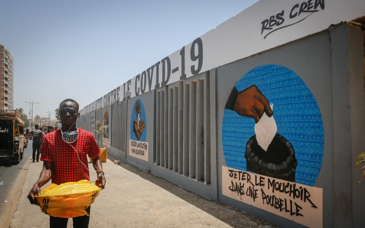 A man walks past a mural depicting a set of good hygiene practices for preventing coronavirus that has been painted on the walls of Dakar's main university campus by graffiti group RBS. The message visible here says: 'Throw tissues away in a rubbish bin.' In a country where literacy levels are low, street art is an effective way to share public health messages. During the Ebola crisis of 2014-2016, artists around West Africa had painted murals to inform people about the deadly effects of the virus. [Maya Hautefeuille/Al Jazeera]