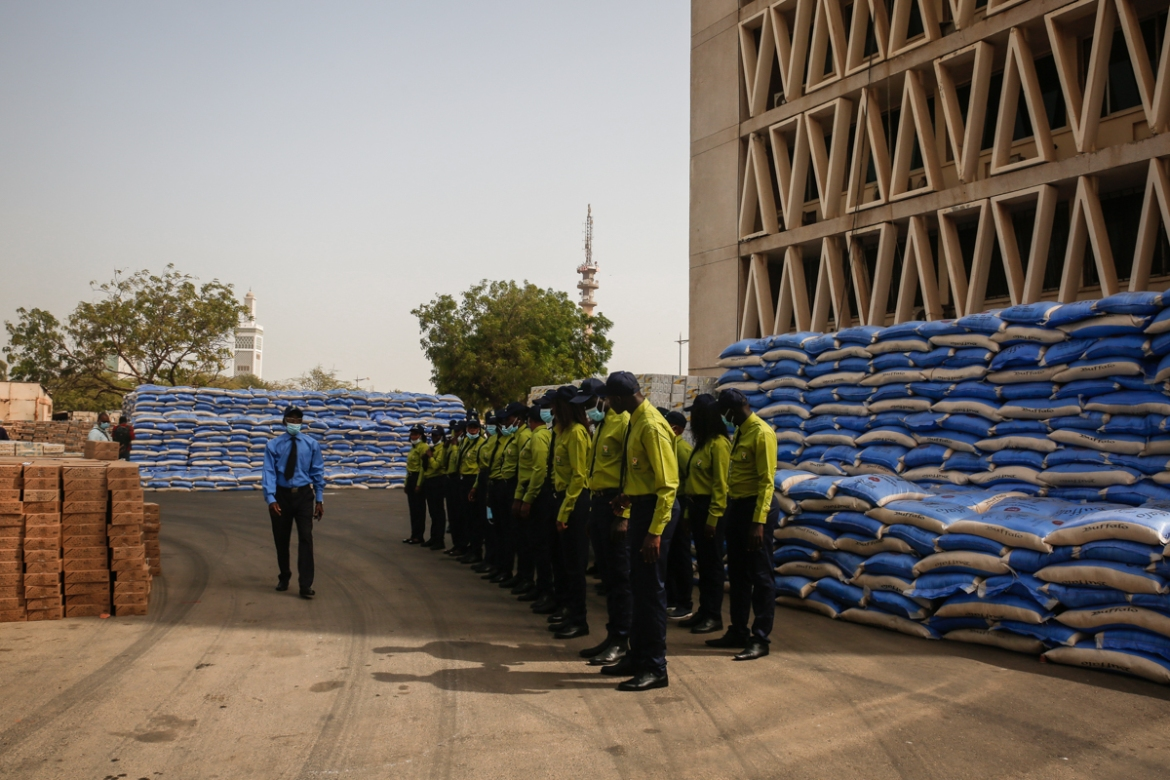 Volunteers from Dakar's city hall stand by food supplies ready for distribution to 19 districts of the city. At the onset of the coronavirus pandemic in the country, the Senegalese government started contingency plans to offer food aid to millions of people. [Maya Hautefeuille/Al Jazeera]