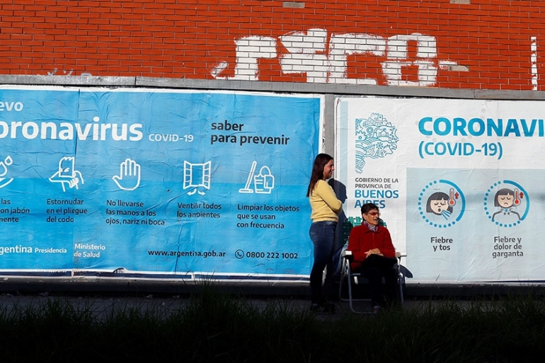 Two women stand next to a sign warning about the novel coronavirus in Buenos Aires, Argentina  [Agustin Marcarian/ReutersA