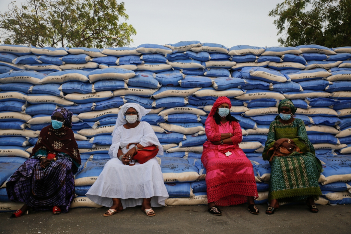 Women sit on sacks of rice during aid distribution to families in need headed by the mayor of Dakar on April 10. In March, President Macky Sall announced economic measures to mitigate the coronavirus crisis including the provision of 50 billion West African CFA franc ($84m) for food aid. [Maya Hautefeuille/Al Jazeera]
