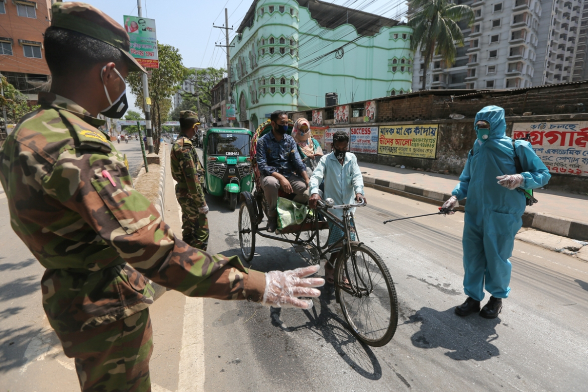 Bangladesh army sprays passing vehicles with disinfectant during concerns over spread of coronavirus in Dhaka. [Mahmud Hossain Opu/Al Jazeera]
