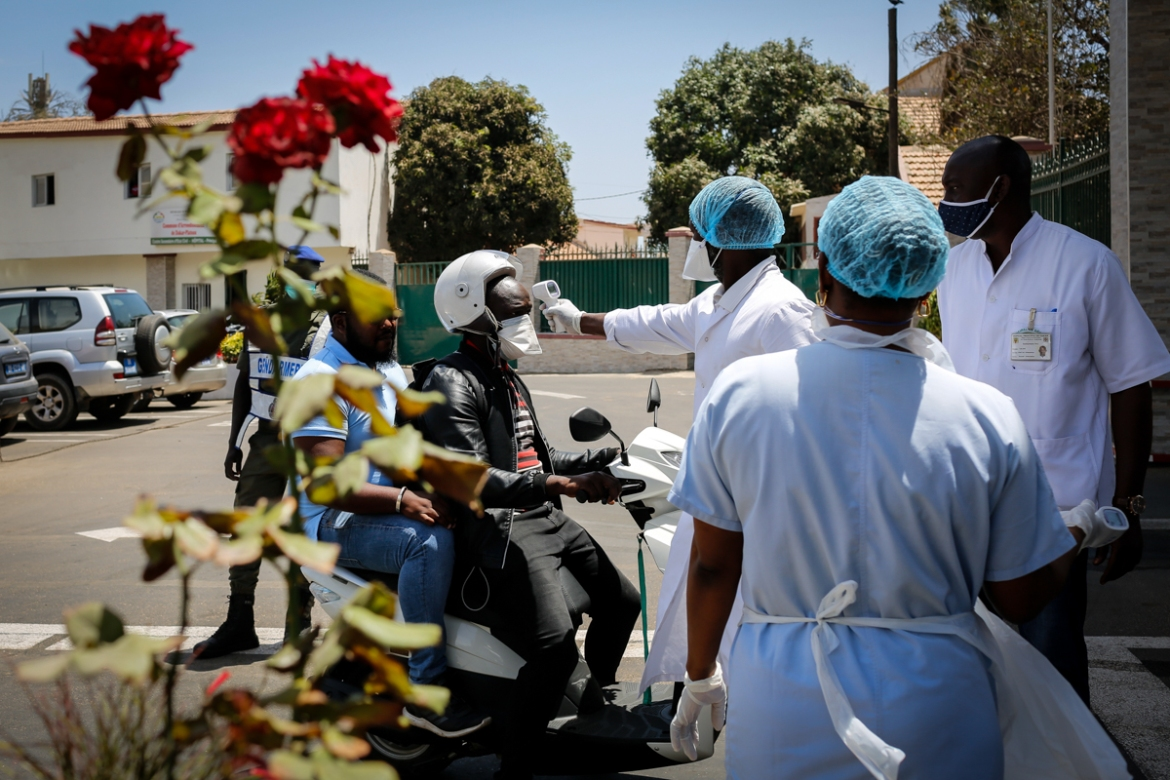 Medical staff and police officers conduct temperature checks at the entrance of the Hopital Principal of Dakar before allowing patients, visitors and staff to enter. The hospital started reporting COVID-19 cases at the start of April. [Maya Hautefeuille/Al Jazeera]