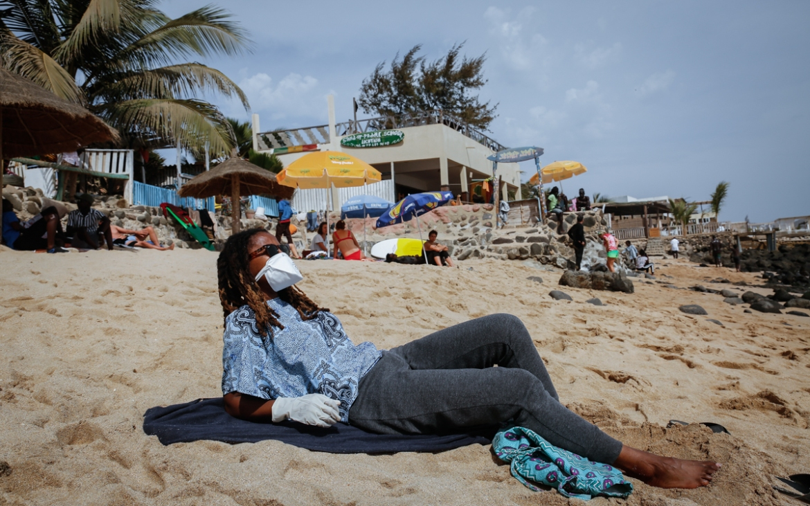 A fully-covered beachgoer relaxes wearing a face mask and gloves at a Dakar beach, while keeping distance. Public spaces have remained opened but gatherings of more than 10 people are banned. A stricter governmental directive from April 11 has allowed police patrols to stop or detain beachgoers. [Maya Hautefeuille/Al Jazeera]