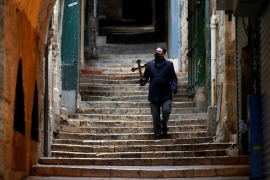 Souvenir shops on the Via Dolorosa were shuttered as just a handful of friars were allowed to walk the traditional procession route [Ammar Awad/Reuters]