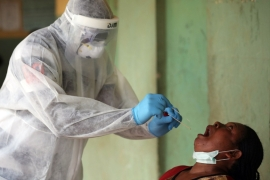 A health worker takes a swab during a community coronavirus testing campaign in Abuja [File: Kola Sulaimon/AFP via Getty Images]
