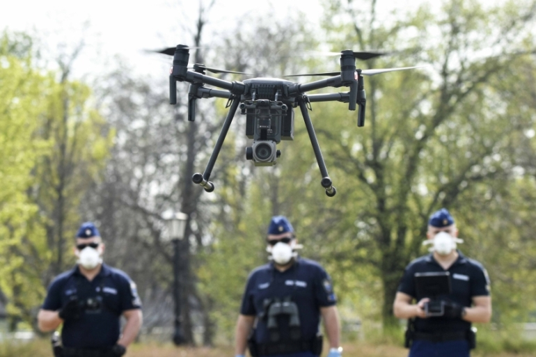 Police officers prepare a drone to find residents who fail to comply with the stay-at-home order implemented due to the coronavirus pandemic in Szolnok, Hungary on April 13, 2020 [AP/Janos Meszaros]