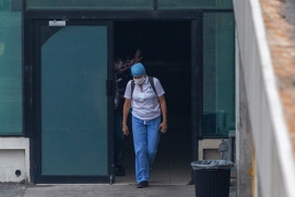 A health worker exits an area of the closed La Aurora airport, where the government is holding Guatemalan citizens deported from the United States in a temporary shelter as they wait for their new coronavirus test results, in Guatemala City, Guatemala [Moises Castillo/AP Photo]