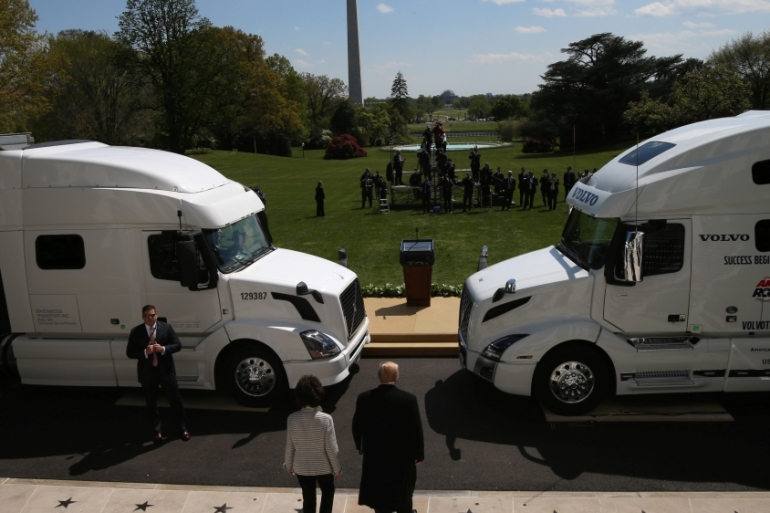 Trump, at the White House, walks between two long-haul trucks with Transportation Secretary Elaine Chao as they arrive for an event 'celebrating America's truckers' [File: Leah Millis/Reuters]