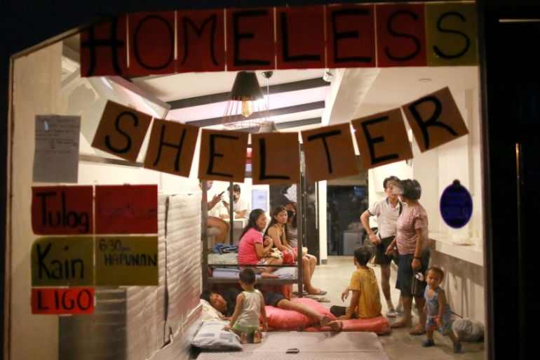 Filipino street dwellers rest in a restaurant that was turned into a makeshift evacuation centre in Quezon City, the Philippines [Eloisa Lopez/Reuters]