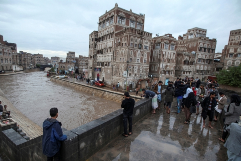 People watch rising floodwaters during heavy rains in the old quarter of the capital, Sanaa [Khaled Abdullah/Reuters]
