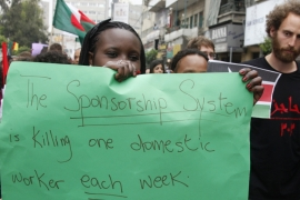 A migrant domestic worker holds up a placard during a parade, in advance of May Day, in Beirut on April 29, 2012 [File: Mohamed Azakir/Reuters]