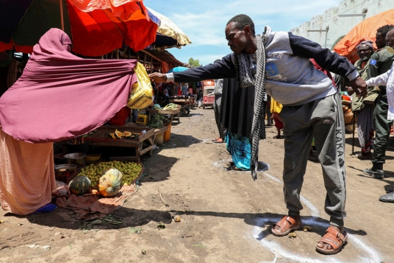A vendor in Mogadishu sells fruit to a customer standing at a physical distancing signage [Feisal Omar/Reuters]