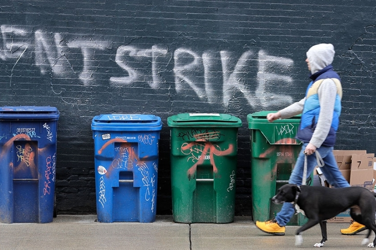 A pedestrian walks past graffiti that reads 'rent strike' Wednesday in the Capitol Hill neighbourhood of Seattle, Washington, the United States [Ted S Warren/AP Photo]