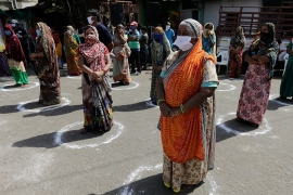 In this April 11, 2020 file photo, women maintain distance as they wait to receive face masks, gloves and hand sanitizers from the Rapid Action Force in Ahmedabad, India. (AP Photo/Ajit Solanki)