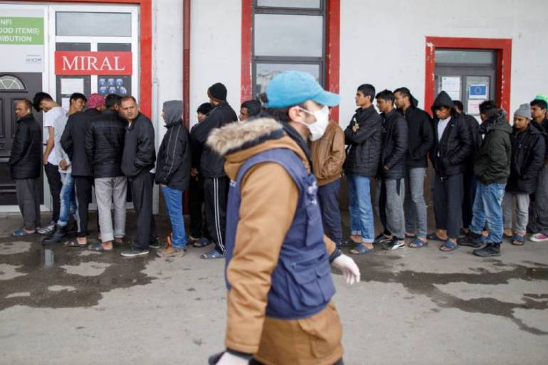 Men wait in line for clothing distribution at the Miral refugee camp in Velika Kladusa, Bosnia [File: Antonio Bronic/Reuters]