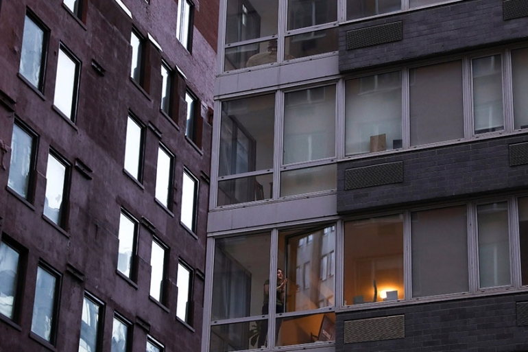 A woman opens her apartment window during the outbreak of coronavirus disease (COVID-19) in Manhattan, New York [File: Caitlin Ochs/Reuters]