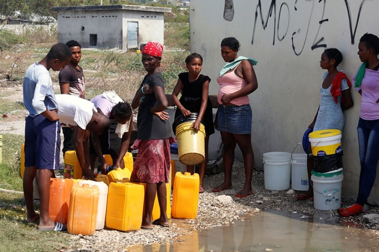 People wait to get water from a communal tap, during an outbreak of the coronavirus disease (COVID-19), in Port-au-Prince, Haiti [Jeanty Junior Augustin/Reuters]