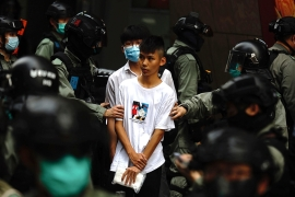 Riot police guard arrested a young protester near Centre district as a second reading of a controversial national anthem law takes place in Hong Kong, Wednesday, May 27, 2020. Hong Kong police massed outside the legislature complex Wednesday, ahead of debate on a bill that would criminalize abuse of the Chinese national anthem in the semi-autonomous city. (AP Photo/Kin Cheung) [The Associated Press]
