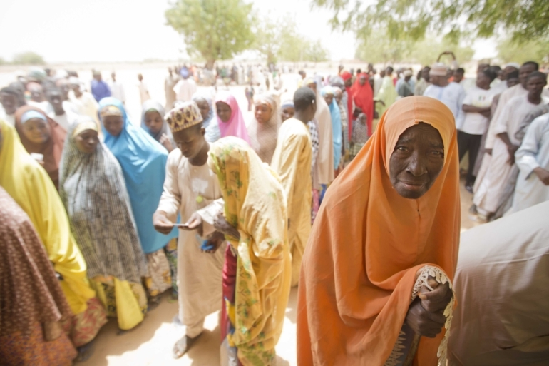 An elderly Nigerian woman stands in the shade while waiting to cast her vote at a polling station in Daura, northern Nigeria on March 28, 2015 [File: AP/Ben Curtis]