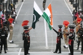 Pakistani Rangers, wearing black uniforms, and Indian Border Security Force officers lower their national flags at the Pakistan-India joint checkpost at Wagah border [File: Mohsin Raza/Reuters]