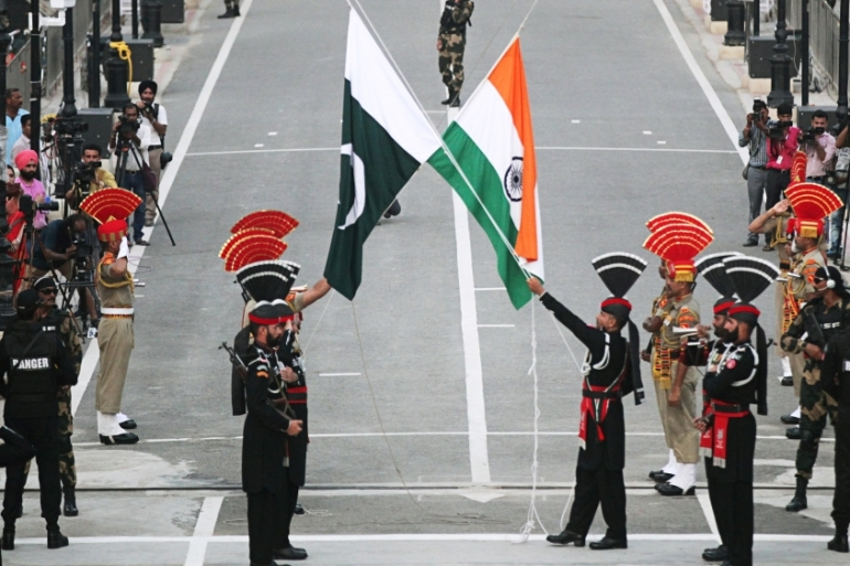 Pakistani Rangers (wearing black uniforms) and Indian forces lower their national flags during a parade on Pakistan's 72nd Independence Day, at the Pakistan-India check-point at Wagah border near Lahore [File: Mohsin Raza/Reuters]