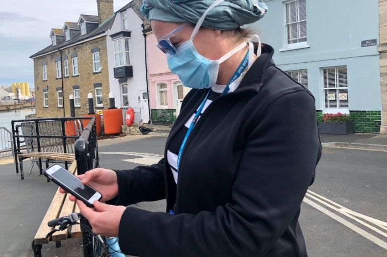 An employee of the UK National Health Service looks at the new NHS app to trace contacts with people potentially infected with COVID-19,  Isle of Wight,UK, May 5, 2020 [Isla Binnie/Reuters]