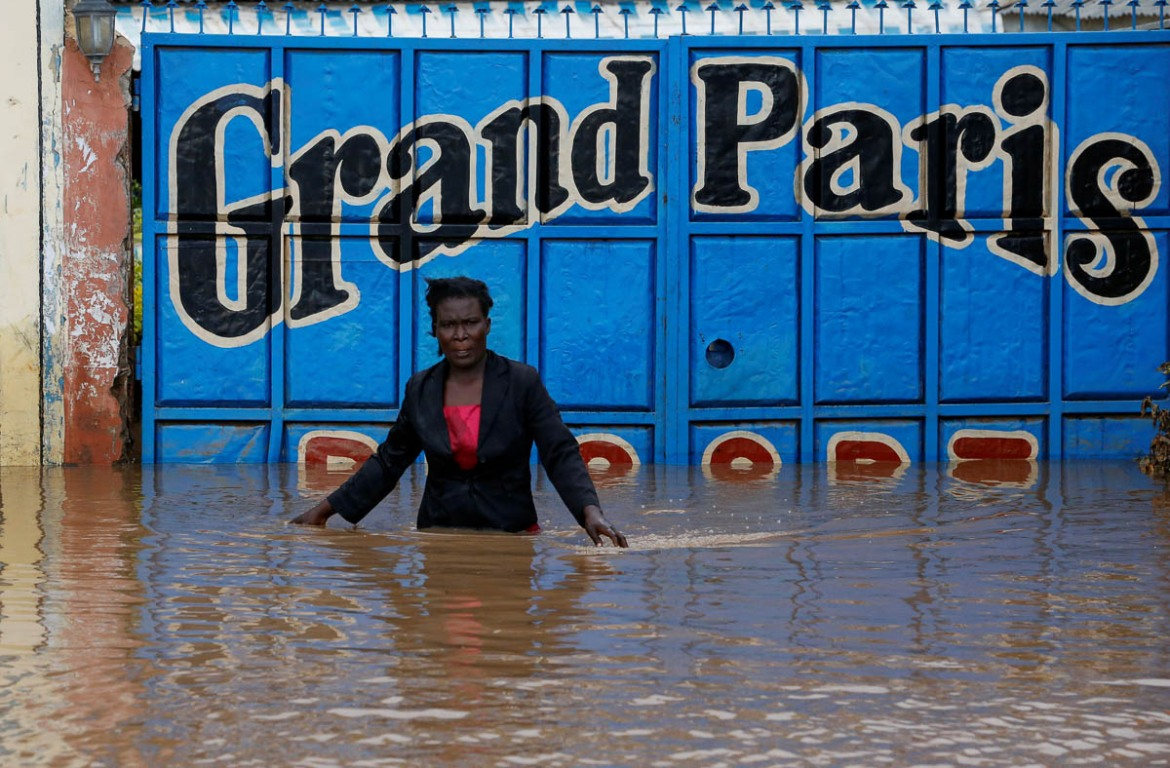 """Our things have been spoiled in here, for example the fridge, deep freezer and the cookers. Cooking pots have been swept away by the water and we are doomed,"" said Maureen Atieno, as she secured the doors of her restaurant, now submerged in floodwaters. [Thomas Mukoya/Reuters]"