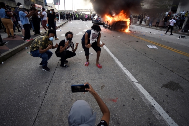An Atlanta Police Department vehicle burns as people pose for a photo during a demonstration against police violence in in Atlanta, Georgia, the United States [Mike Stewart/AP Photo]