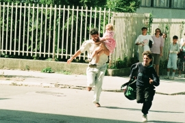 With Serb snipers positioned on top of the hills surrounding Sarajevo, a man with a child takes a risk to run across the street [File: Danilo Krstanovic]