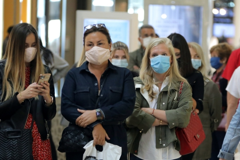 Women wearing protective face masks wait to enter in a shop in Saint Laurent du Var near Nice as France softens its strict lockdown rules, May 11, 2020 [Eric Gaillard/Reuters]