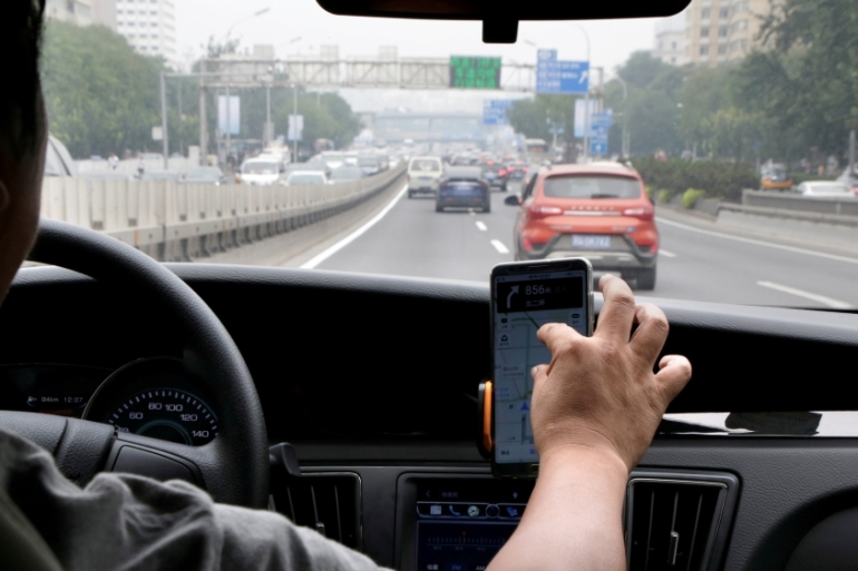Didi's ride-hailing drivers in Latin America will need to take a selfie with mask on to pass an AI verification, and from June they will need to report their body temperature to the phone app [File: Jason Lee/Reuters]
