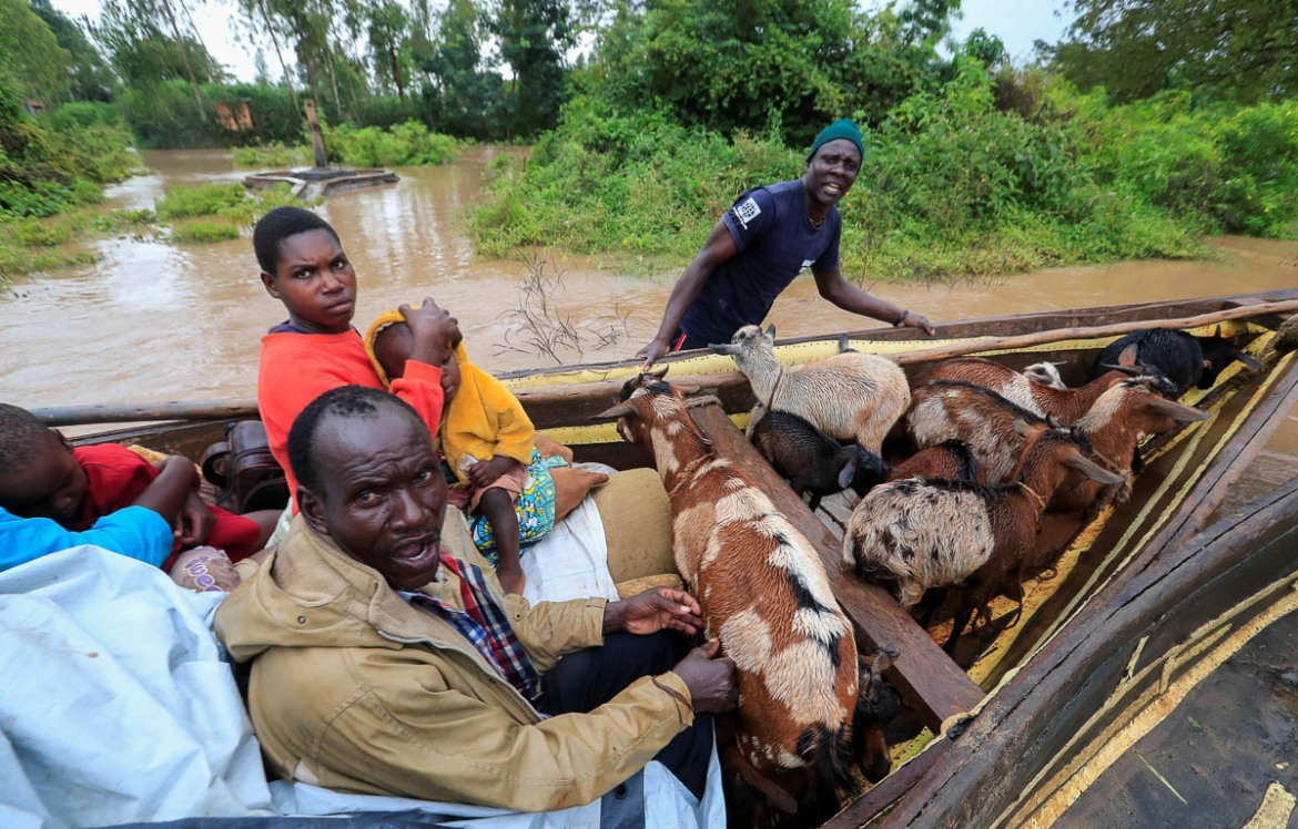 Residents piled into boats with whatever they could rescue, including animals, to escape the floodwaters in Buyuku. [Thomas Mukoya/Reuters]