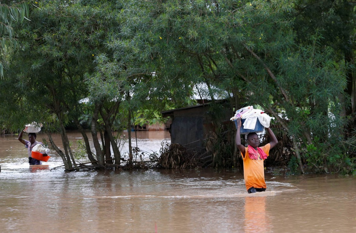 Residents wade through waist-high water with their belongings held high as they evacuate from their homes in Nyadorera. [Thomas Mukoya/Reuters]