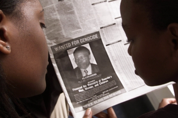 Readers look at a newspaper carrying the photograph of Rwandan Felicien Kabuga [File: George Mulala/Reuters]