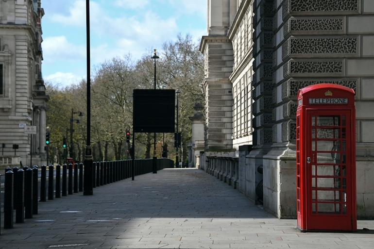 A red phone box stands in an empty street in Westminster, in London on March 29, 2020 [AP Photo/Alberto Pezzali]
