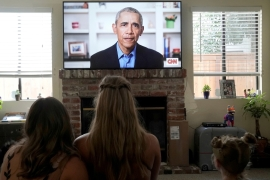 Graduating high school students watch former US President Barack Obama deliver a virtual commencement address to millions of high school seniors who will miss graduation ceremonies due to the coronavirus. Schools across the country are now debating how and whether to reopen later this year [File: Bing Guan/Reuters]