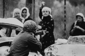 An Israeli soldier aims his rifle at a Palestinian woman holding a rock during a demonstration in which one Palestinian youth was shot dead in Gaza, on February 29, 1988 [Reuters]